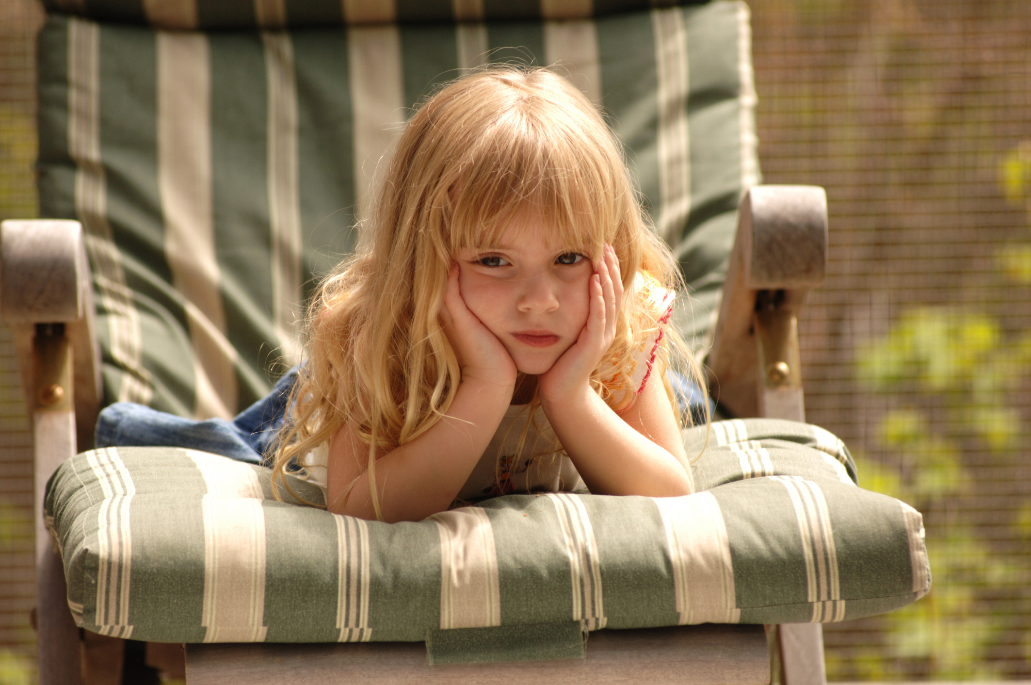 Blond girl on chair with her hands to her face